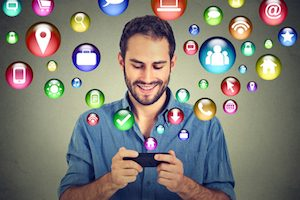 Happy man using texting on smartphone social media application icons flying out